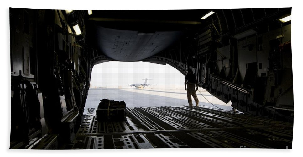 Airfield Beach Towel featuring the photograph A Loadmaster Guides The Pilot Of A C-17 by Terry Moore