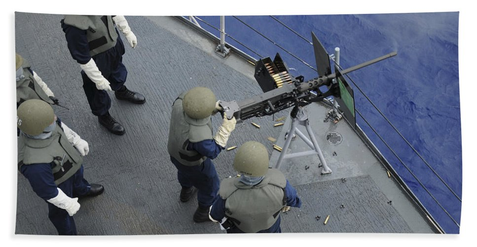 Uss Frank Cable Beach Towel featuring the photograph A U.s. Sailor Fires A .50-caliber M2hb by Stocktrek Images
