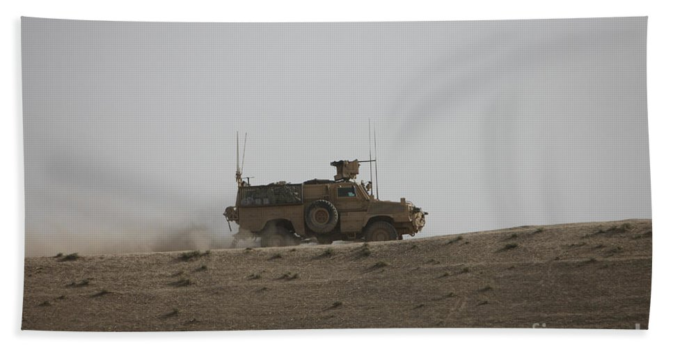 Operation Enduring Freedom Beach Towel featuring the photograph An Mrap Vehicle Patrols The Ridge by Terry Moore