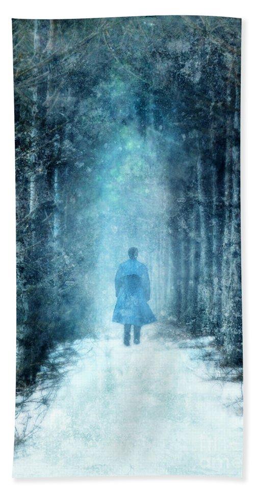 Man Beach Towel featuring the photograph Man Walking Through Snowy Woods by Jill Battaglia
