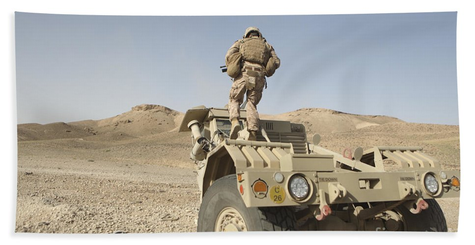 Operation Enduring Freedom Beach Towel featuring the photograph Soldier Climbs A Damaged Husky Tactical by Stocktrek Images