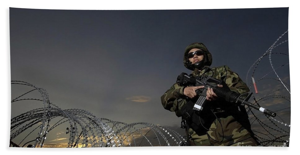 Color Image Beach Towel featuring the photograph Soldier Patrols The Perimeter Of Camp by Stocktrek Images