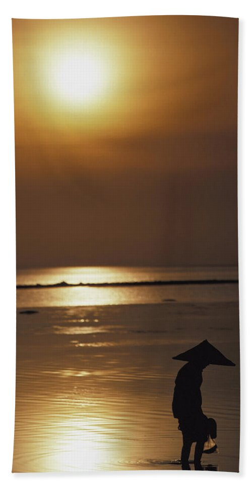 Woman Beach Towel featuring the photograph Woman In Conical Hat Collecting Shell by Axiom Photographic