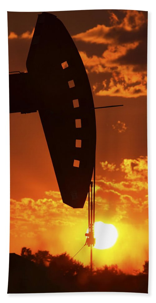 Oil Rig Beach Towel featuring the photograph Oil Rig Pump Jack Silhouetted By Setting Sun by Mark Duffy