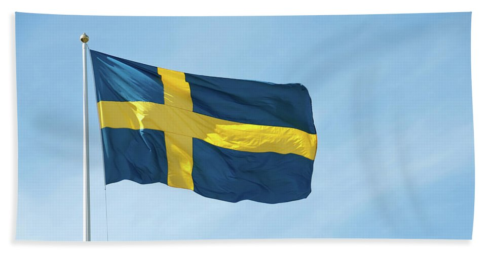 Sweden Beach Towel featuring the photograph Flag of Sweden in the blue sky by GoodMood Art