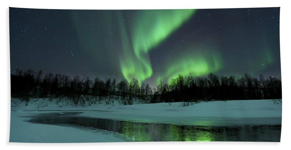 Green Beach Towel featuring the photograph Reflected Aurora Over A Frozen Laksa by Arild Heitmann