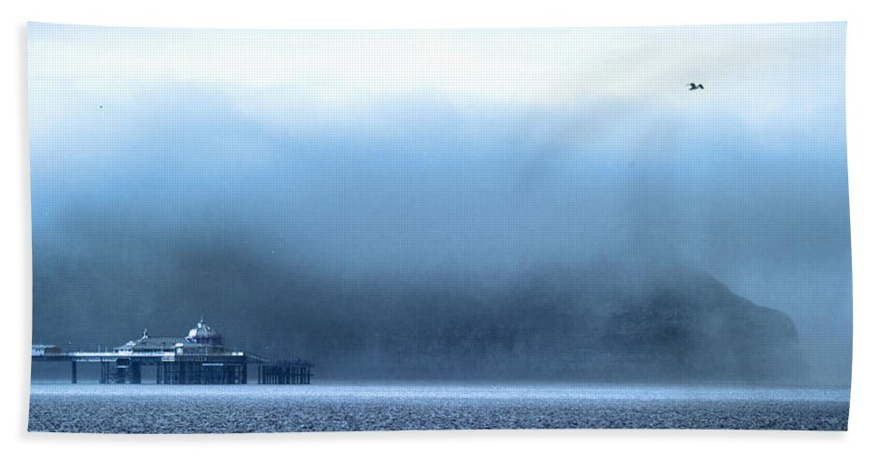 Pier Beach Towel featuring the photograph The Sea Mist Lifts To Reveal The Great Orme Behind Llandudno Pier by Mal Bray