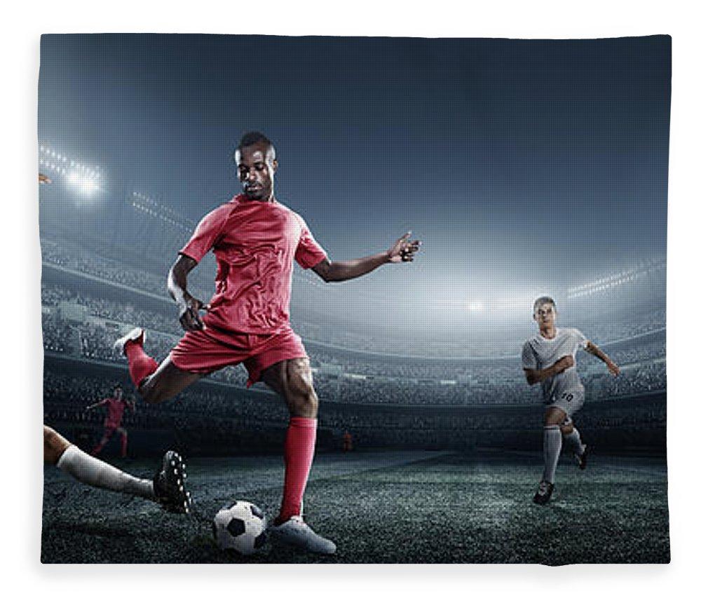 Soccer Uniform Fleece Blanket featuring the photograph Soccer Player Kicking Ball In Stadium by Dmytro Aksonov
