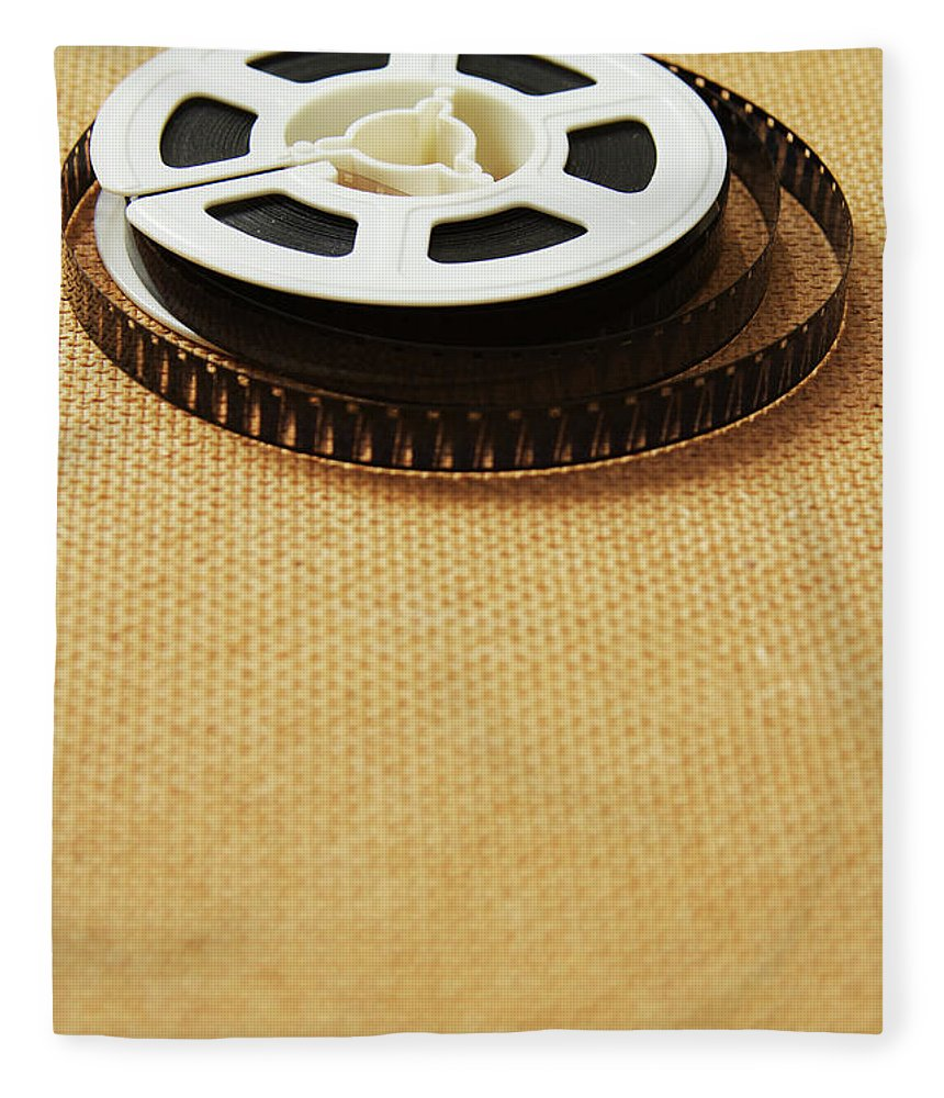 The Media Fleece Blanket featuring the photograph A Reel, Or Spool, Of 8mm Movie Film by Jon Schulte