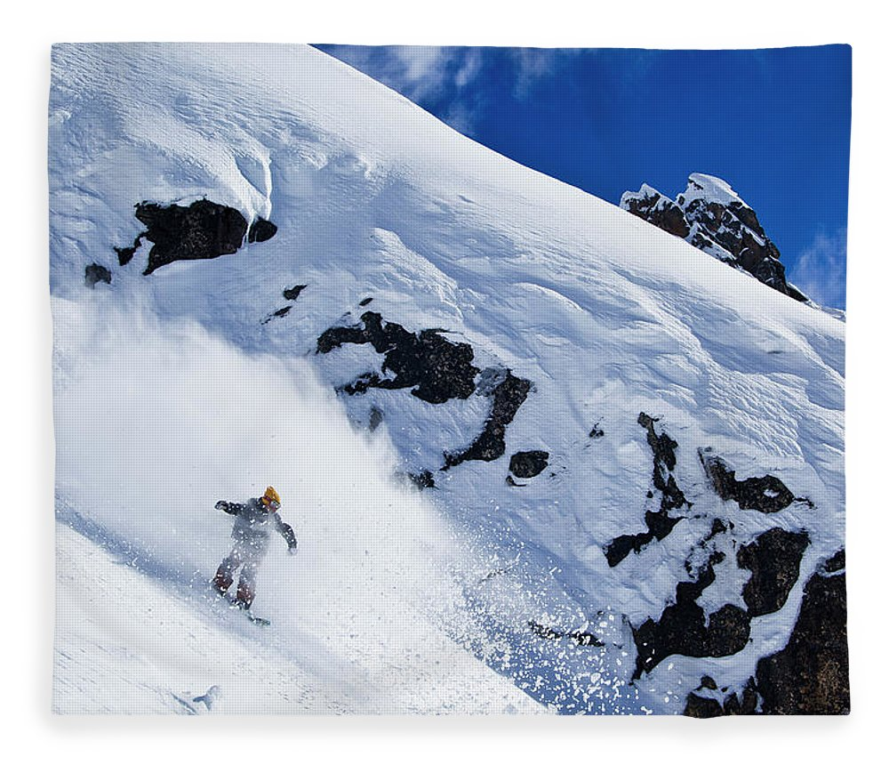Outdoors Fleece Blanket featuring the photograph A Snowboarder Slashes Powder Snow by Ben Girardi