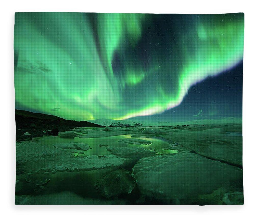 Glacier Lagoon Fleece Blanket featuring the photograph Aurora Display Over The Glacier Lagoon by Natthawat