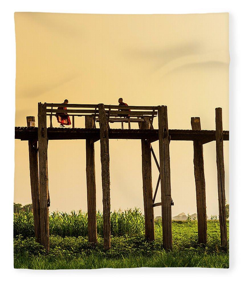 Grass Fleece Blanket featuring the photograph Buddhist Monks Seated On U Bein Bridge by Merten Snijders