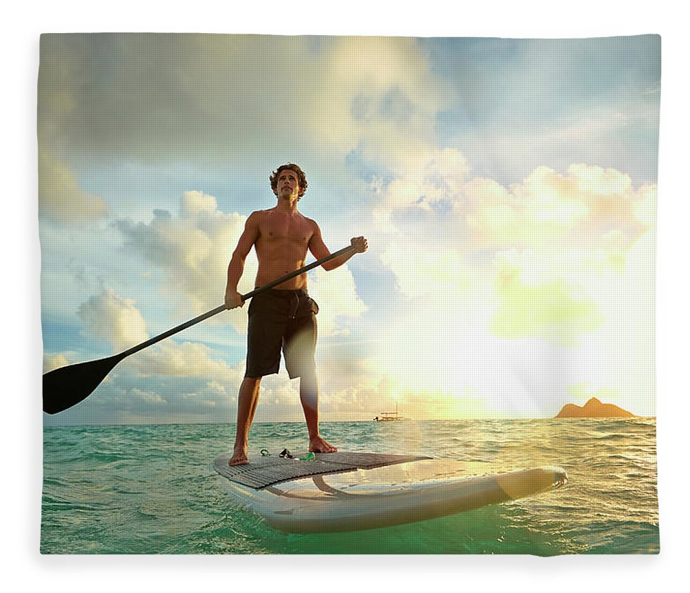 Tranquility Fleece Blanket featuring the photograph Caucasian Man On Paddle Board In Water by Colin Anderson Productions Pty Ltd