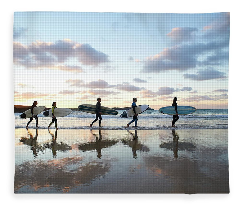 Young Men Fleece Blanket featuring the photograph Five Surfers Walk Along Beach With Surf by Dougal Waters