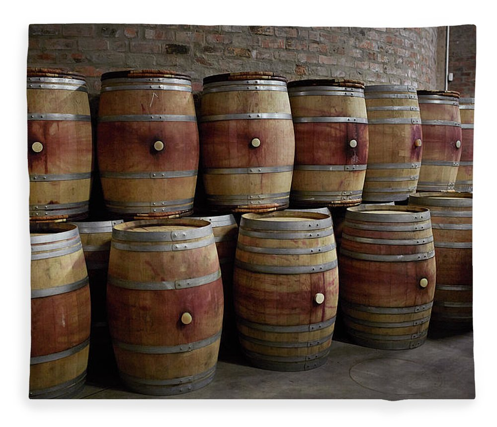 Stellenbosch Fleece Blanket featuring the photograph French Wine Barrels Stacked At Winery by Klaus Vedfelt