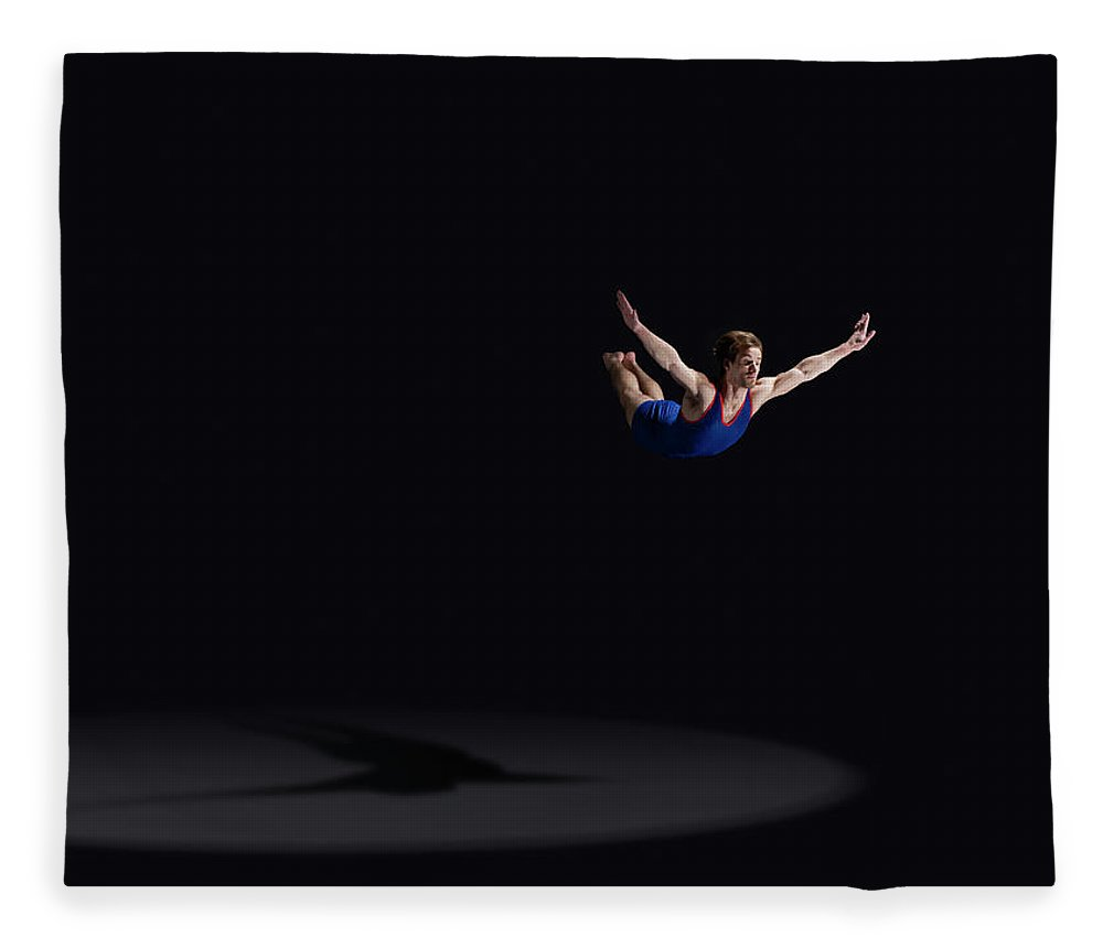 Expertise Fleece Blanket featuring the photograph Male Gymnast Soaring Through The Air by Mike Harrington