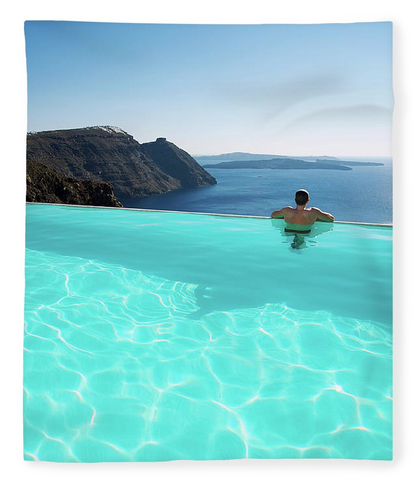 People Fleece Blanket featuring the photograph Man Relaxing Looking At Santorini by Peskymonkey