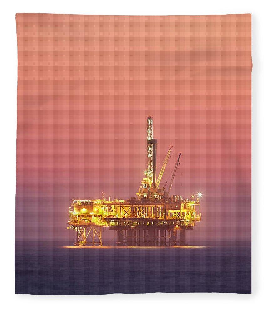 Orange Color Fleece Blanket featuring the photograph Oil Rig Platform In Twilight by Jimkruger