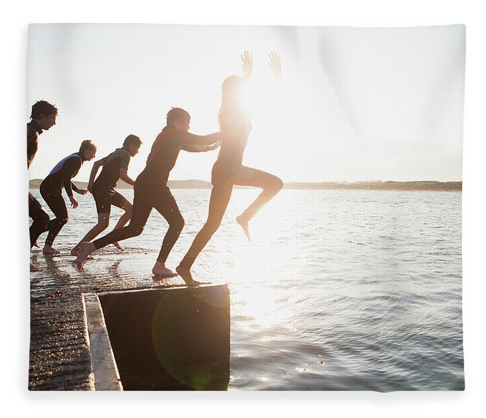 Adolescence Fleece Blanket featuring the photograph Pier Jumping by Solstock