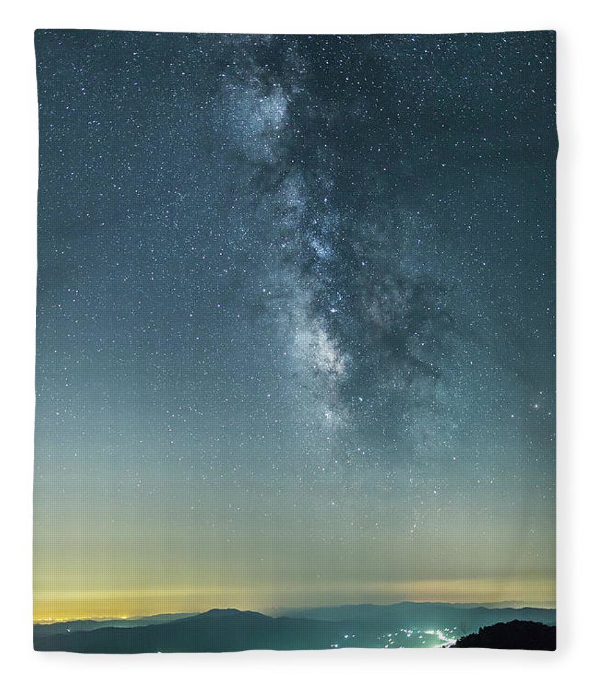 Scenics Fleece Blanket featuring the photograph The Milky Way Hovering Above A Town by Trevor Williams