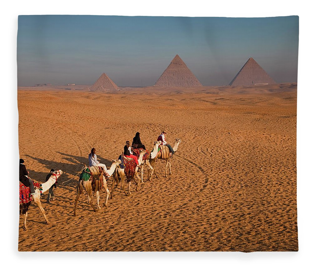 Working Animal Fleece Blanket featuring the photograph Tourists On Camels & Pyramids Of Giza by Richard I'anson