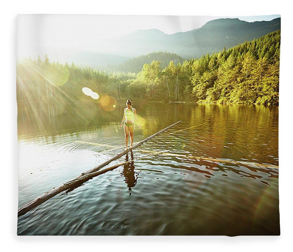 Pets Fleece Blanket featuring the photograph Woman Walking On Log In Alpine Lake by Thomas Barwick
