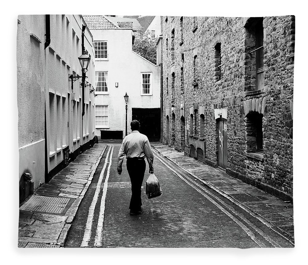 Architecture Fleece Blanket featuring the photograph Man Walking With Shopping Bag Down Narrow English Street by Jacek Wojnarowski