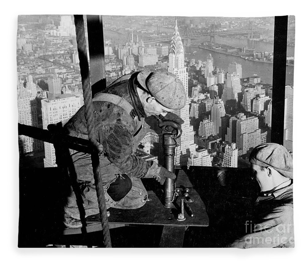 Riveters; Riveting; Male; Work; Labour; Workers; Working; Labourers; Construction; Building; History; Historical; Landmark; Skyscraper; High-rise; Empire State Building; 1930s; 30s; Thirties; Us; Usa; America; American; United States; High; Challenge; Risk; Danger; Courage; Bravery; Heights; Achievement; Scale; Teamwork; Chrysler Building; Aerial View; New York; Manhattan; Architecture; Urban; City; Cityscape; Dramatic; Builder; Builders; Scenic; Concentration; Black And White Photograph; B/w Photo; Photography Fleece Blanket featuring the photograph Riveters On The Empire State Building by LW Hine