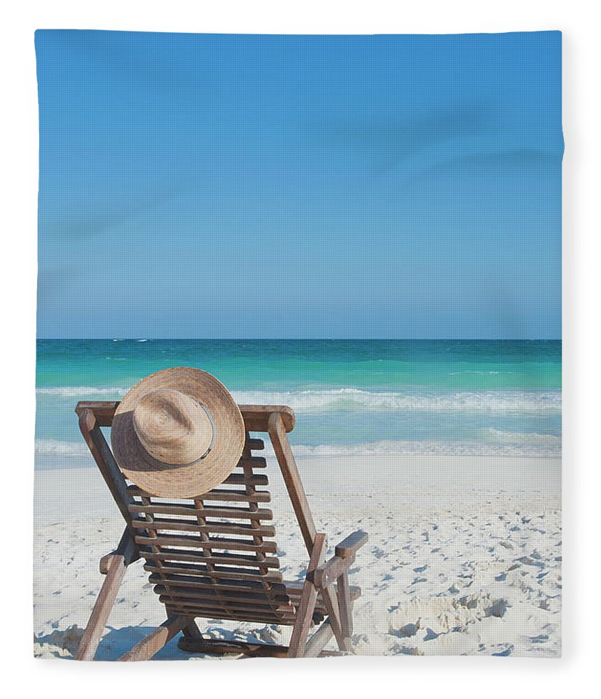 Scenics Fleece Blanket featuring the photograph Beach Chair With A Hat On An Empty Beach by Sasha Weleber