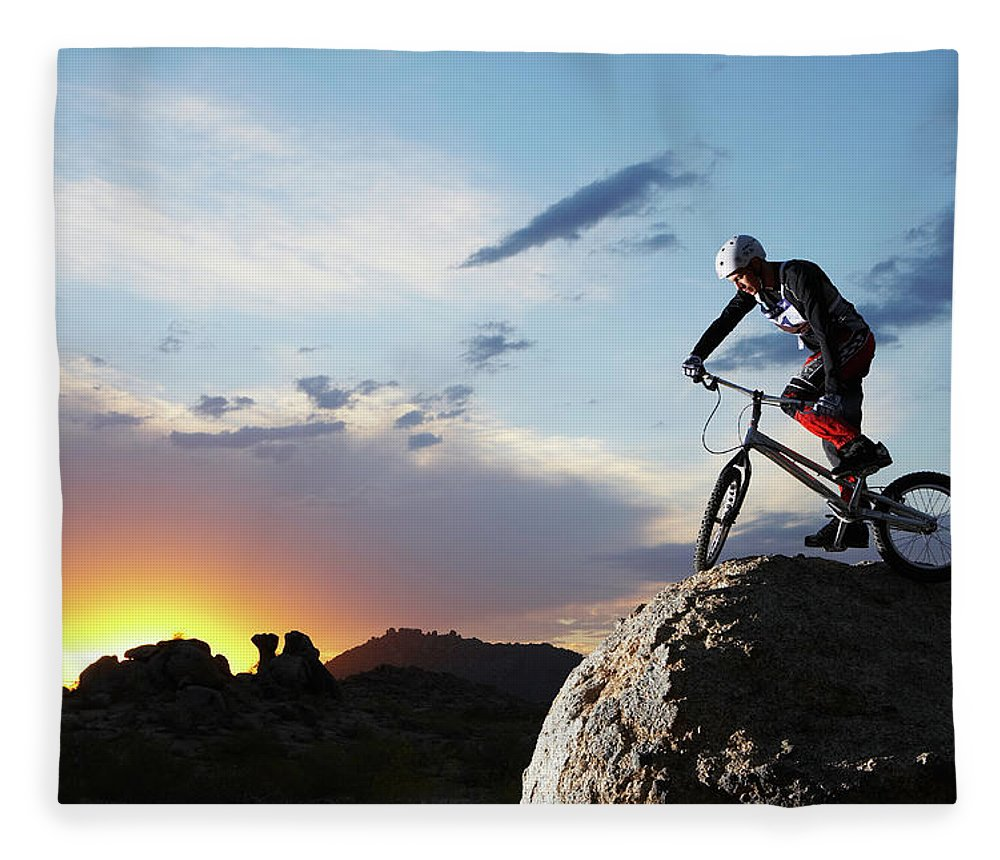 Sports Helmet Fleece Blanket featuring the photograph Bike Rider Balancing On Rock Boulder by Thomas Northcut