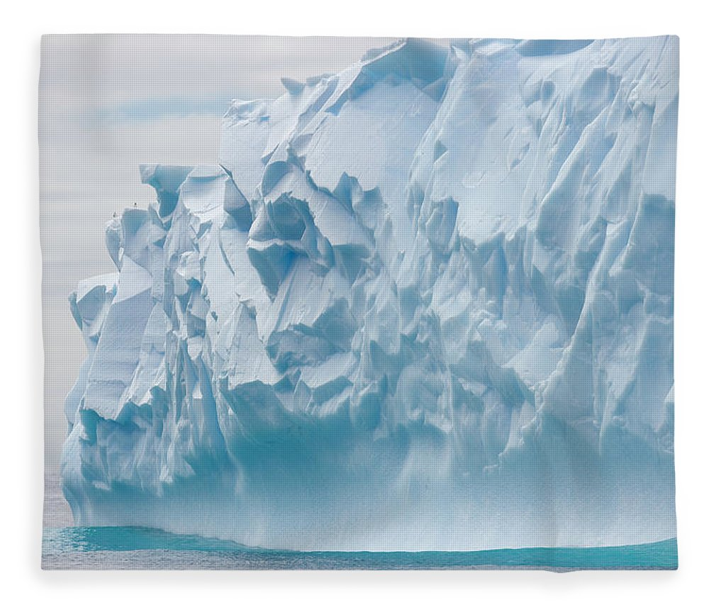 Scenics Fleece Blanket featuring the photograph Blue Iceberg Carved By Waves Floats In by Eastcott Momatiuk
