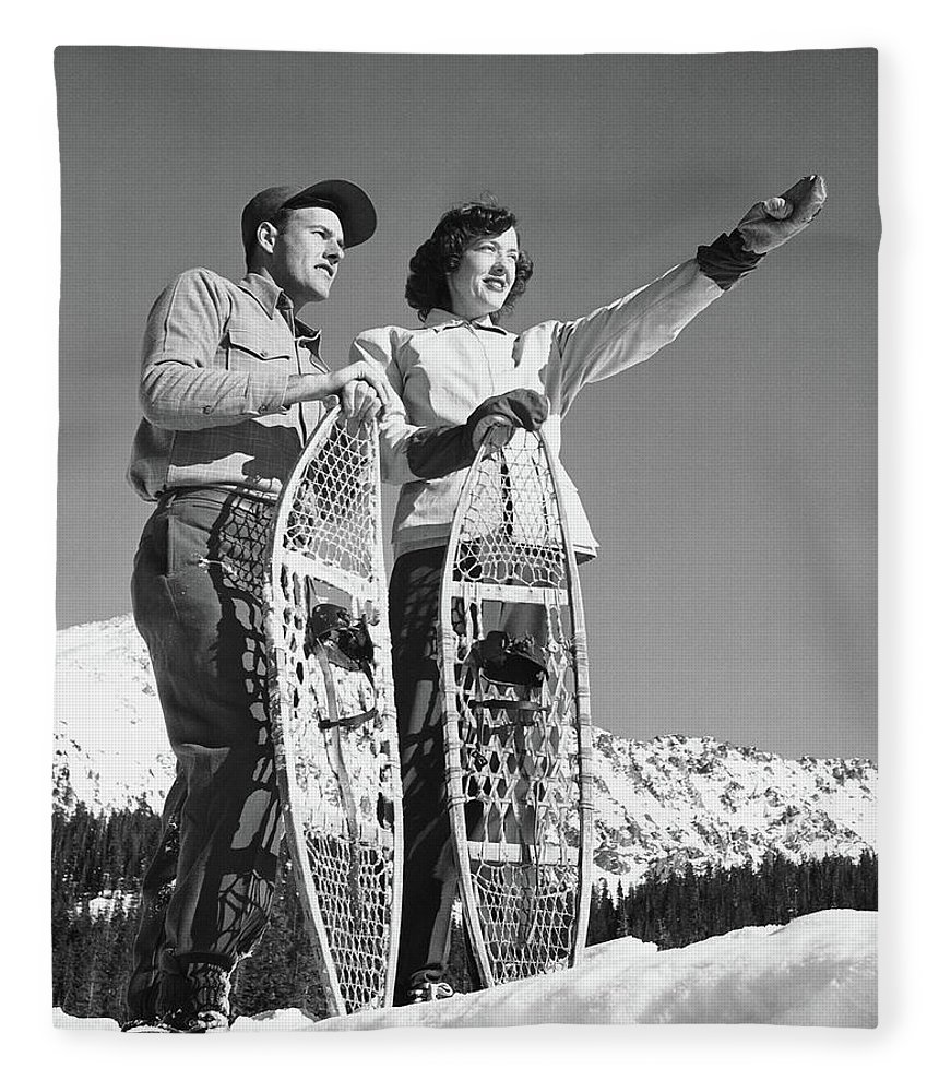 Heterosexual Couple Fleece Blanket featuring the photograph Couple Holding Snowshoes, Woman Pointing by Stockbyte