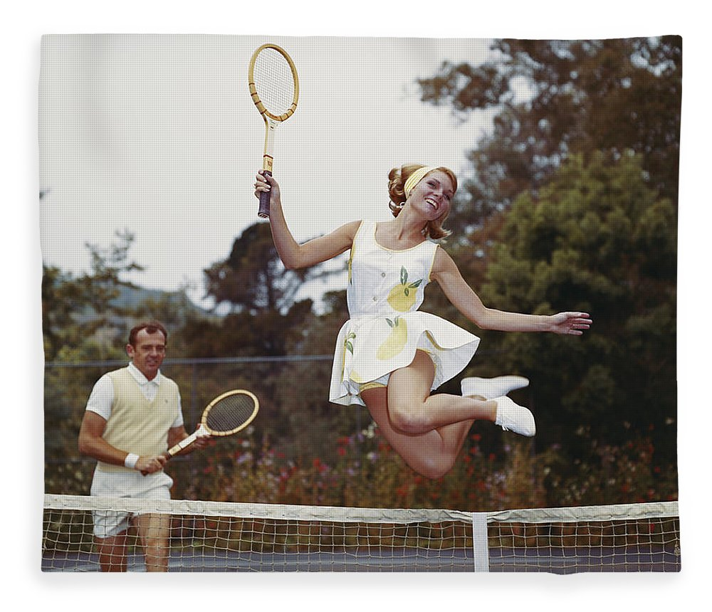 Heterosexual Couple Fleece Blanket featuring the photograph Couple On Tennis Court, Woman Jumping by Tom Kelley Archive