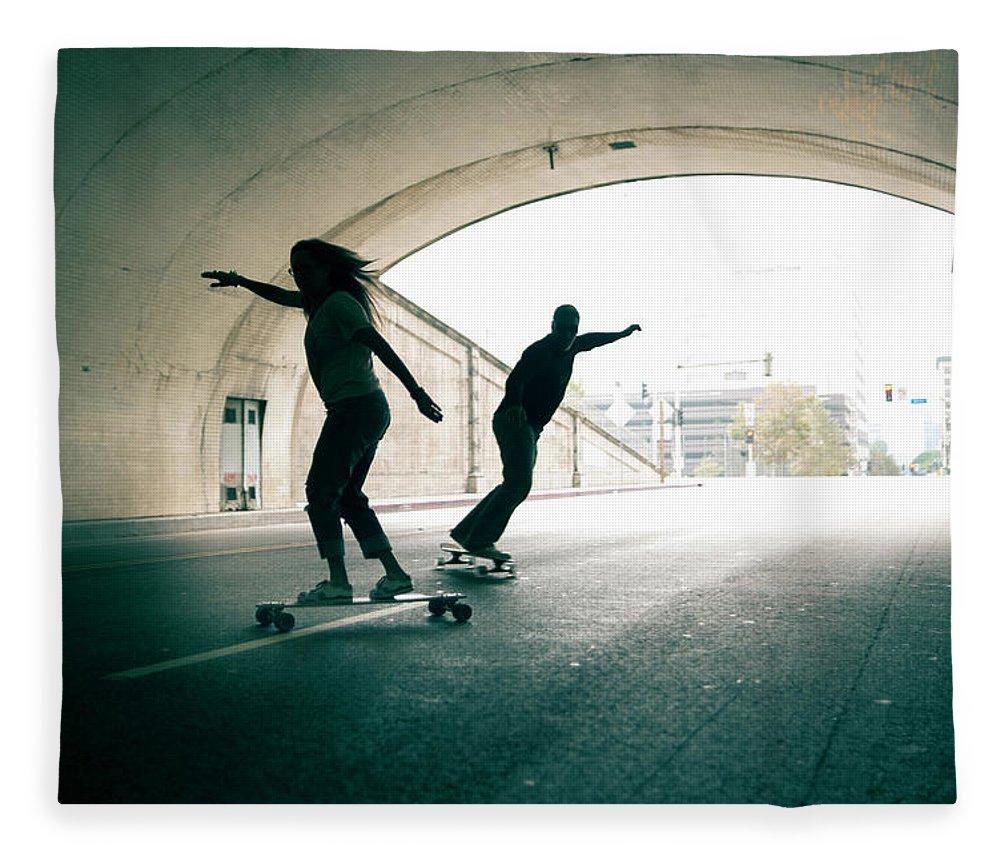 Mature Adult Fleece Blanket featuring the photograph Couple Skateboarding Through Tunnel by Ian Logan