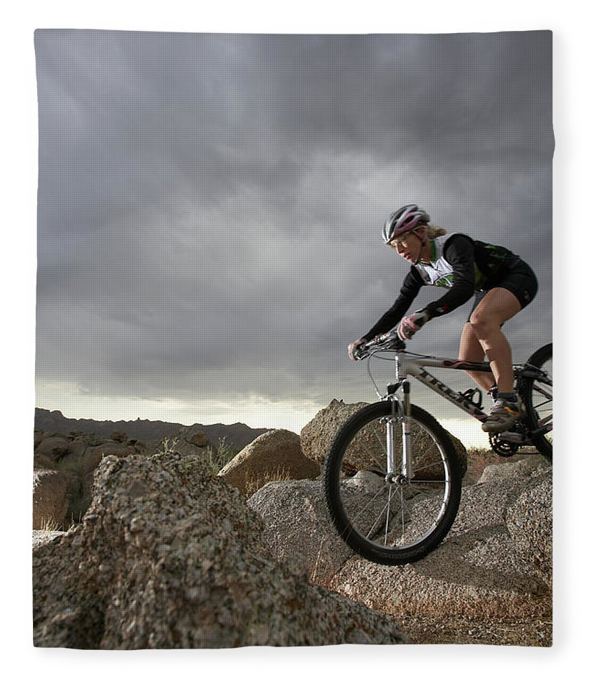 Sports Helmet Fleece Blanket featuring the photograph Female Rider Mountain Biking Between by Thomas Northcut