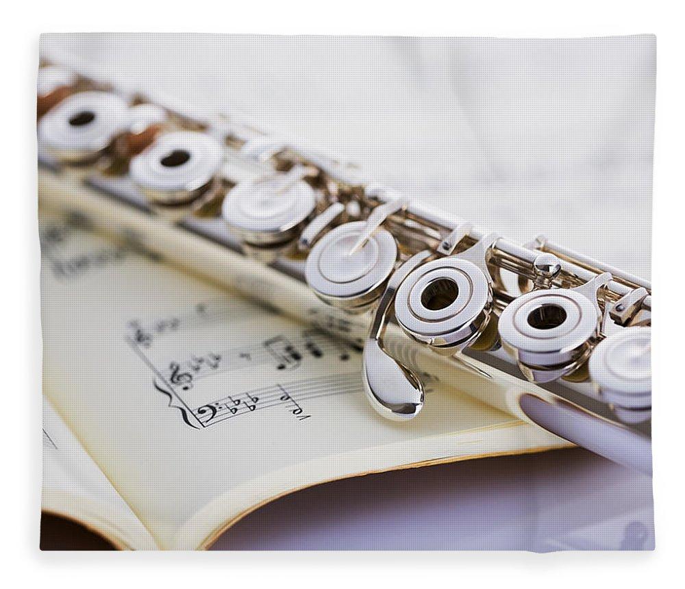 Sheet Music Fleece Blanket featuring the photograph Flute On A Score by Imagenavi