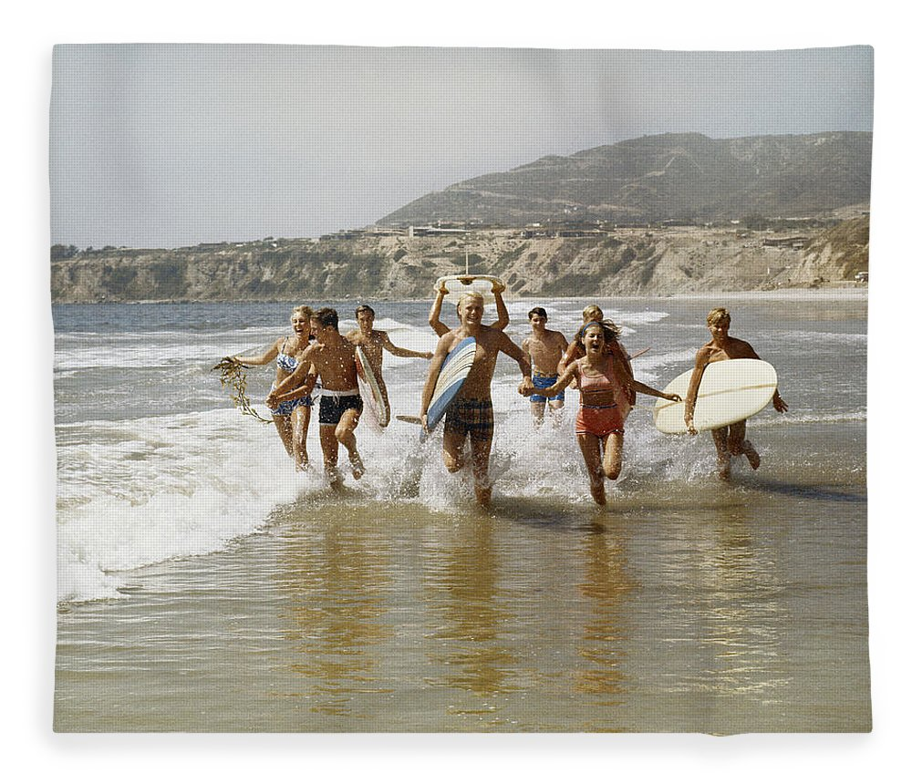Young Men Fleece Blanket featuring the photograph Group Of Surfers Running In Water With by Tom Kelley Archive