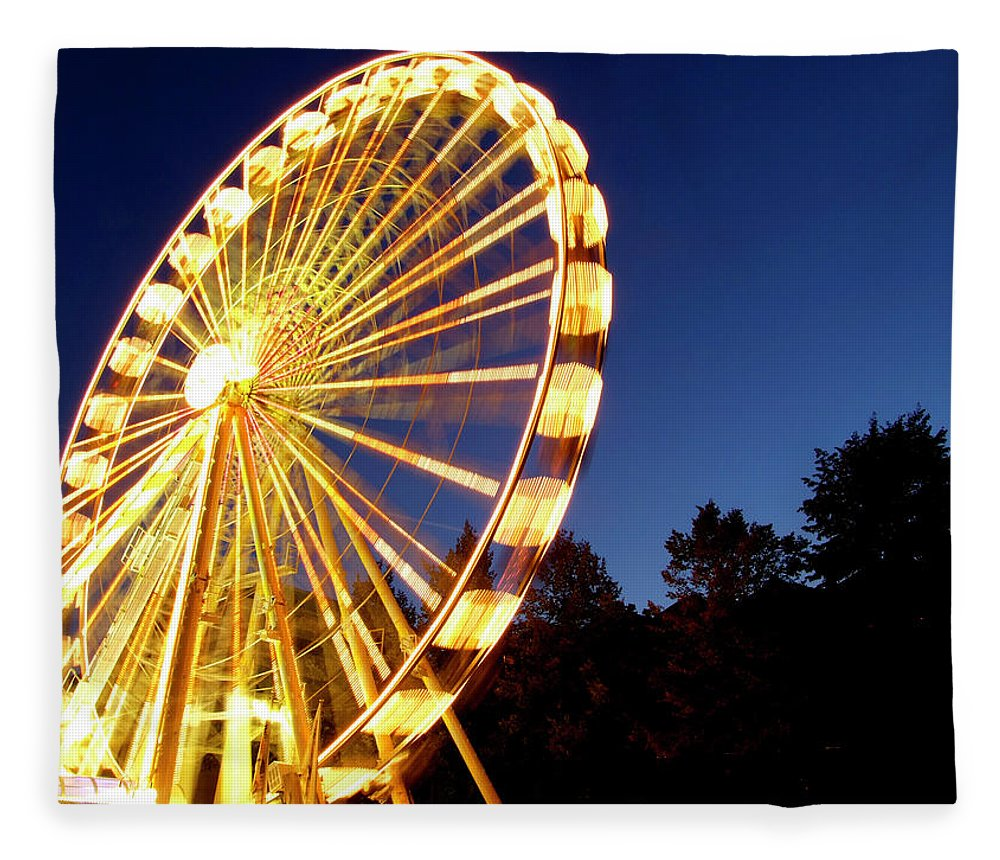 Curve Fleece Blanket featuring the photograph Lighted Ferris Wheel Spinning In Motion by Vfka