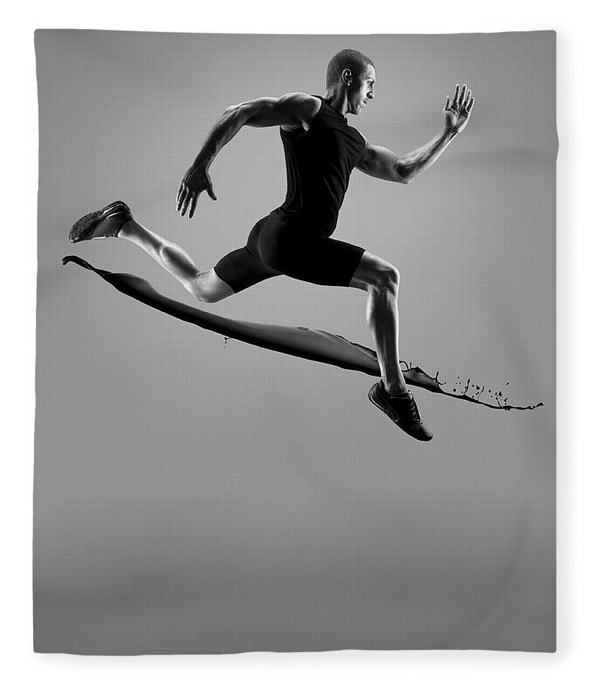 People Fleece Blanket featuring the photograph Male Athlete Running Above Liquid Splash by Jonathan Knowles