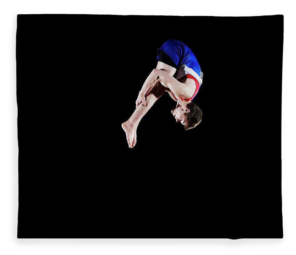 Focus Fleece Blanket featuring the photograph Male Gymnast 16-17 Mid Air, Black by Thomas Barwick