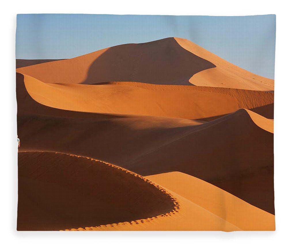 Shadow Fleece Blanket featuring the photograph Man Climbing Sand Dunes, Namib Desert by Peter Adams