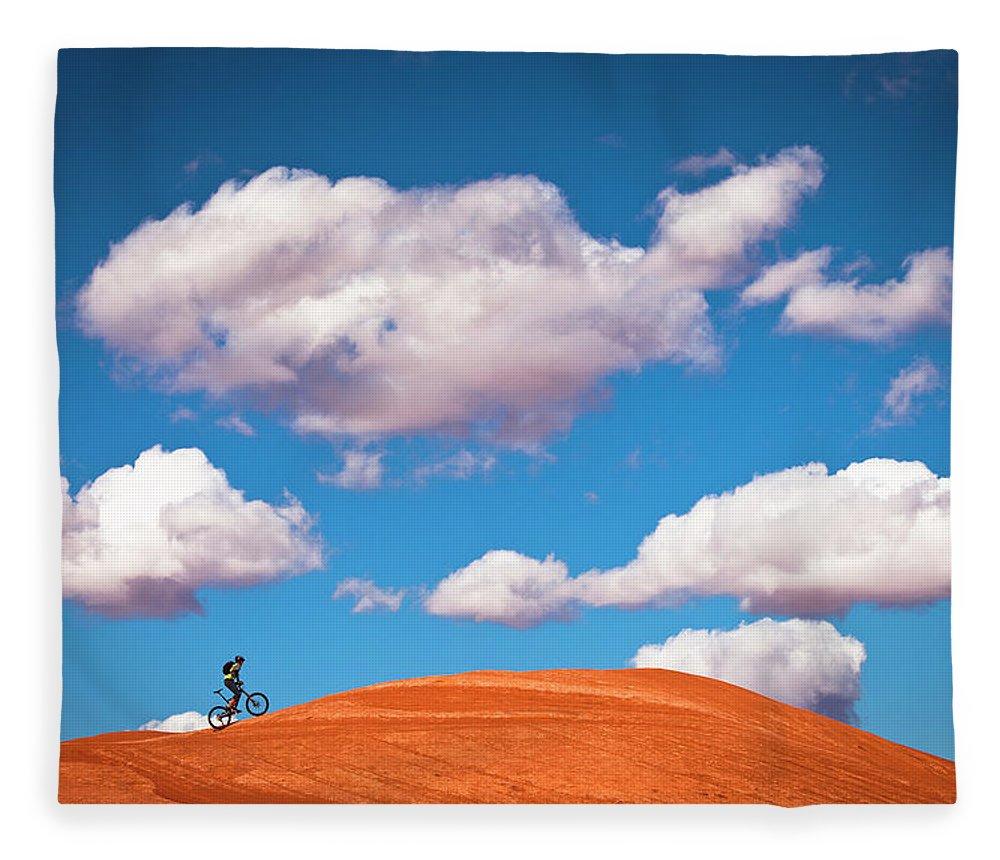 Slickrock Trail Fleece Blanket featuring the photograph Mountain Biker Climbing On Slick Rock by Visualcommunications
