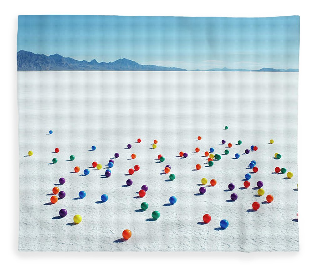 Out Of Context Fleece Blanket featuring the photograph Multi-colored Balls On Salt Flats by Andy Ryan