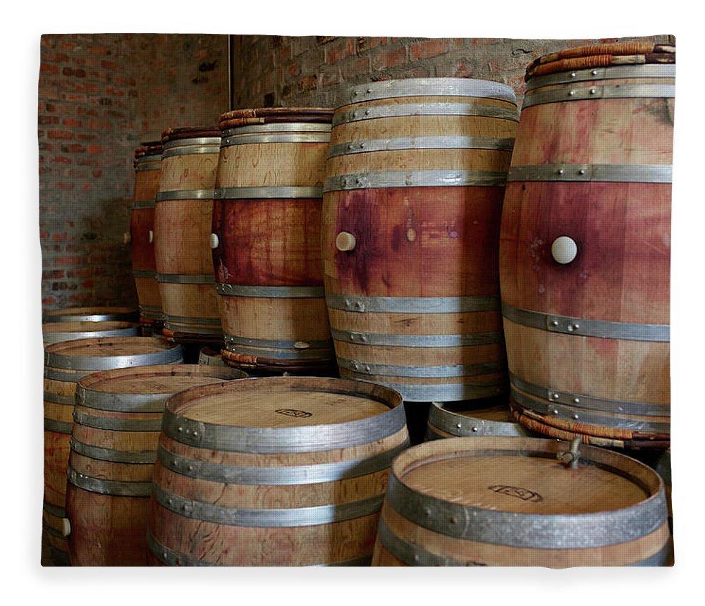 Stellenbosch Fleece Blanket featuring the photograph Pile Of Wooden Barrels At Winery by Klaus Vedfelt