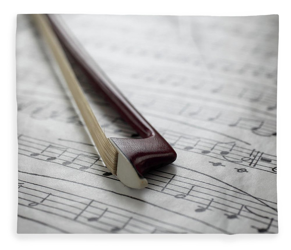 Sheet Music Fleece Blanket featuring the photograph Violin Bow On Music Sheet by Daniel Allan