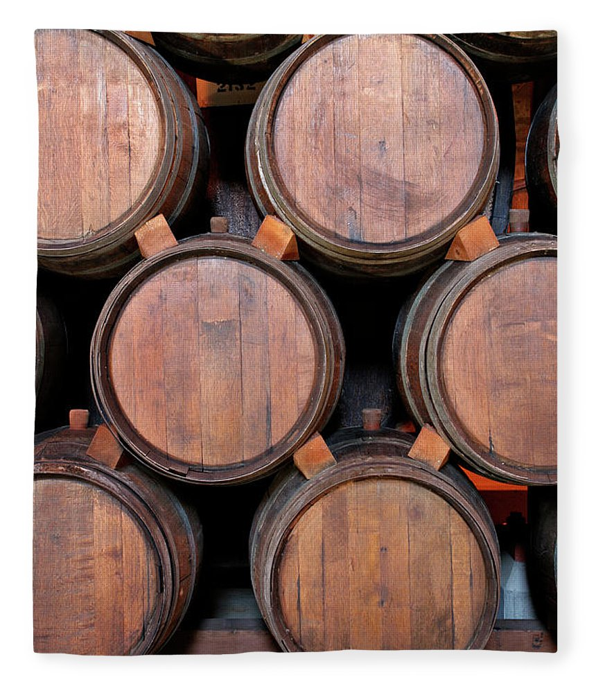 Fermenting Fleece Blanket featuring the photograph Wine Barrels Stacked Inside Winery by Yinyang