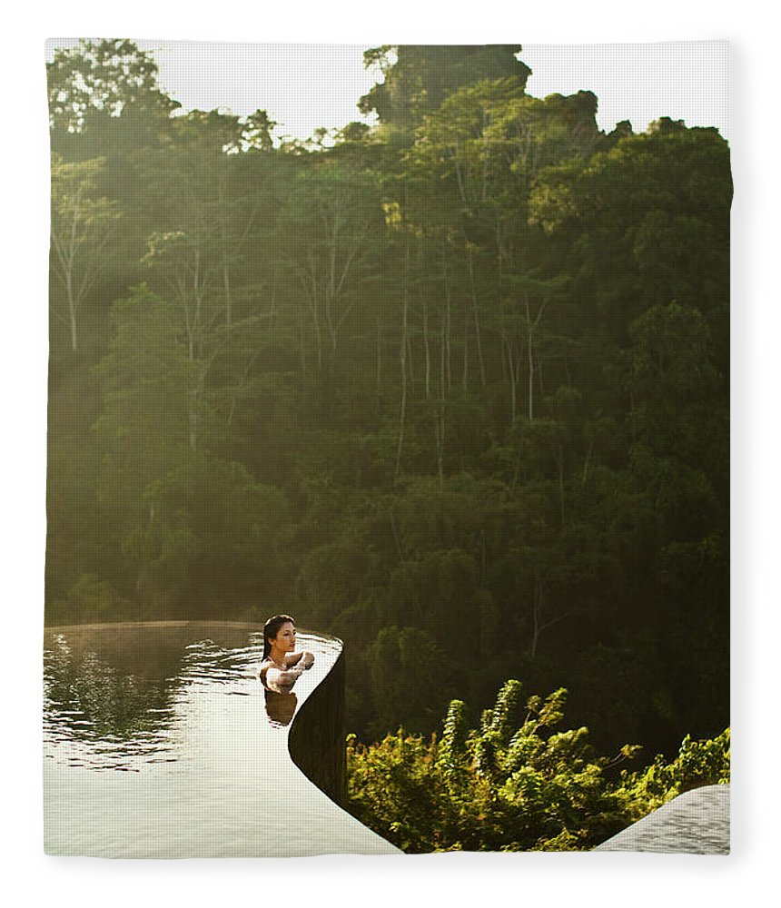 Tropical Rainforest Fleece Blanket featuring the photograph Woman In Infinity Pool At Sunrise. Bali by Matthew Wakem