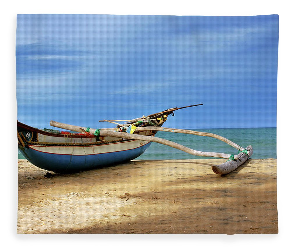 Tranquility Fleece Blanket featuring the photograph Wooden Catamaran By The Sea Shore by Juavenita Alphonsus