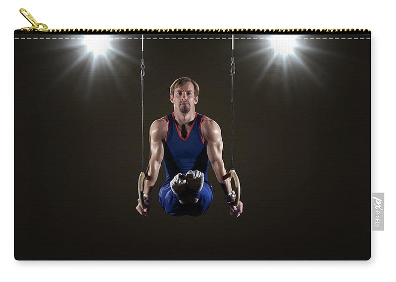 Expertise Carry-all Pouch featuring the photograph Male Gymnast On Rings by Mike Harrington