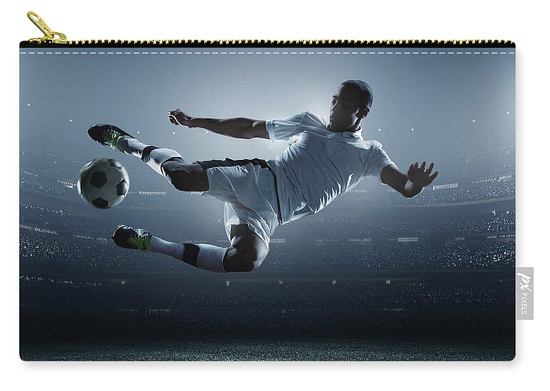 Goal Carry-all Pouch featuring the photograph Soccer Player Kicking Ball In Stadium by Dmytro Aksonov